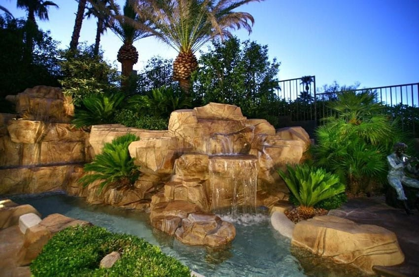 Rock water feature waterfall into pool