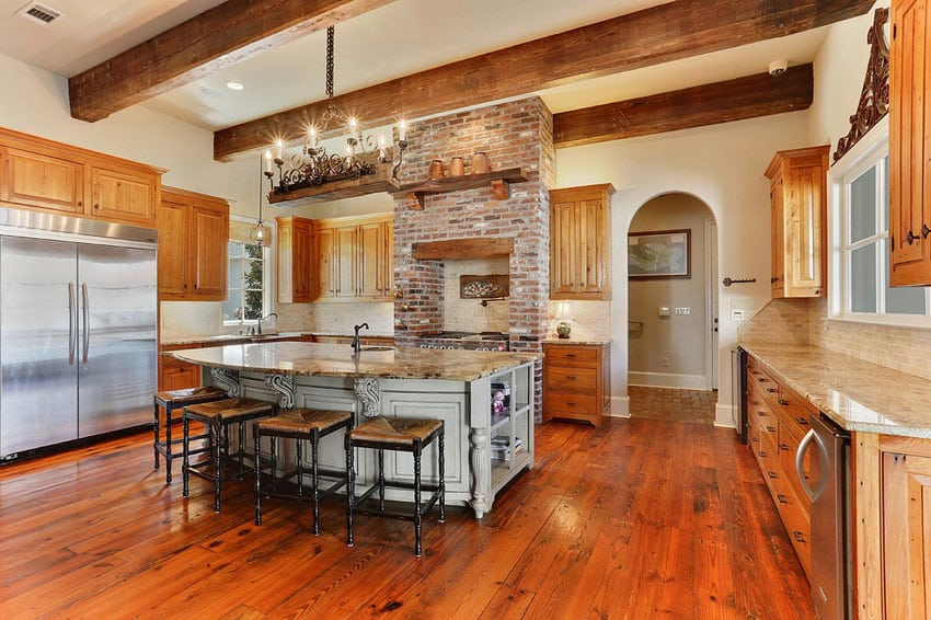 Rustic kitchen with large dining island and brick around stove