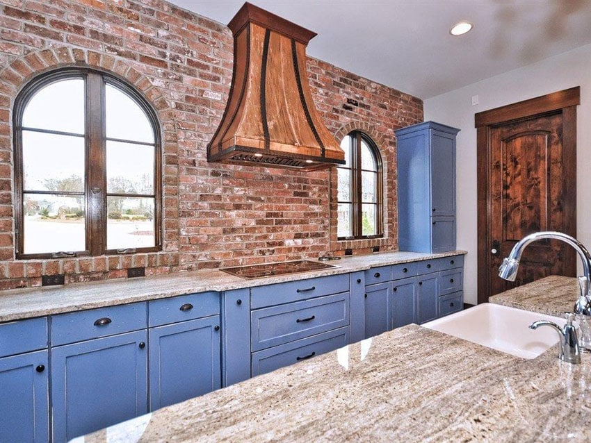Traditional blue cabinet kitchen against brick wall