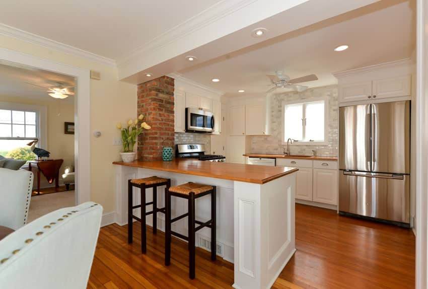 Traditional kitchen with brick veneer and wood countertops