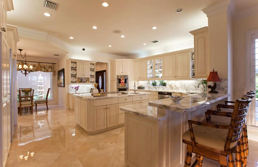 Traditional kitchen with stone floors and off white cabinetry