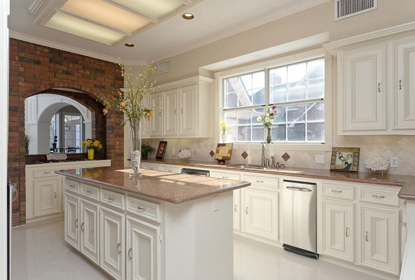 Traditional white kitchen with brick arch and travertine backsplash