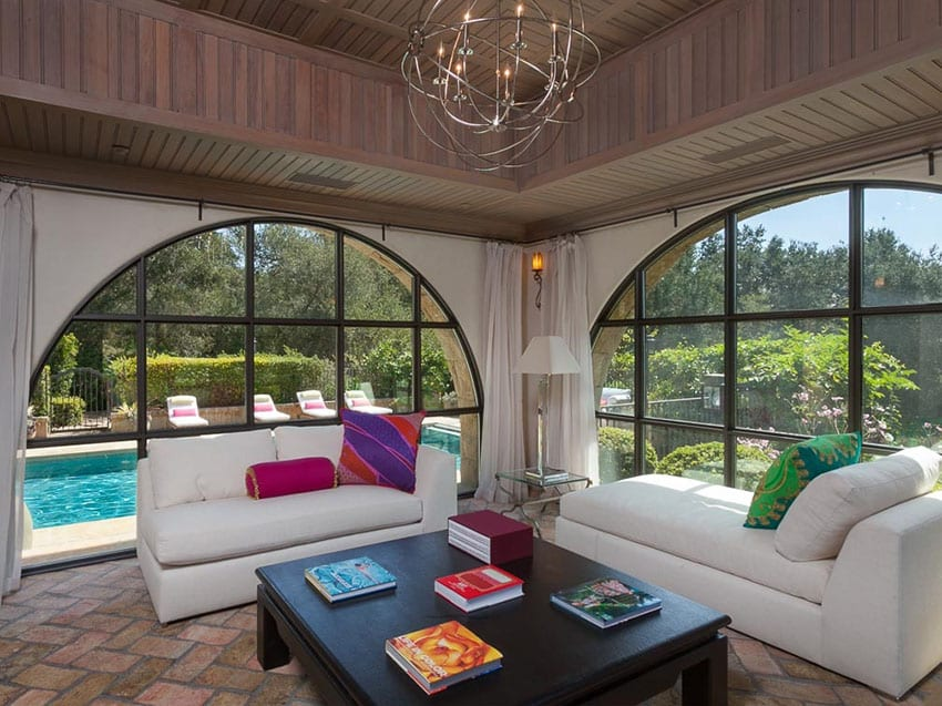 Tuscan sunroom with modern chandelier and swimming pool view