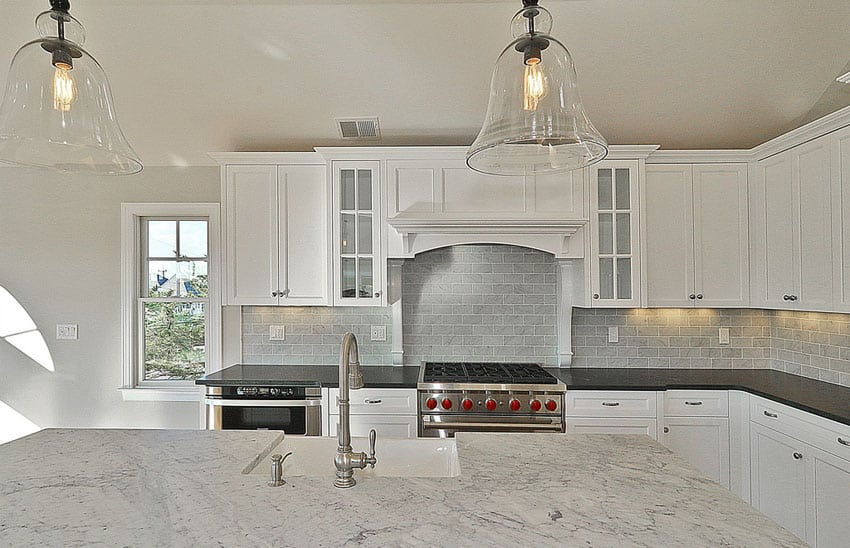 white kitchen with marble counters and brick subway tile backsplash