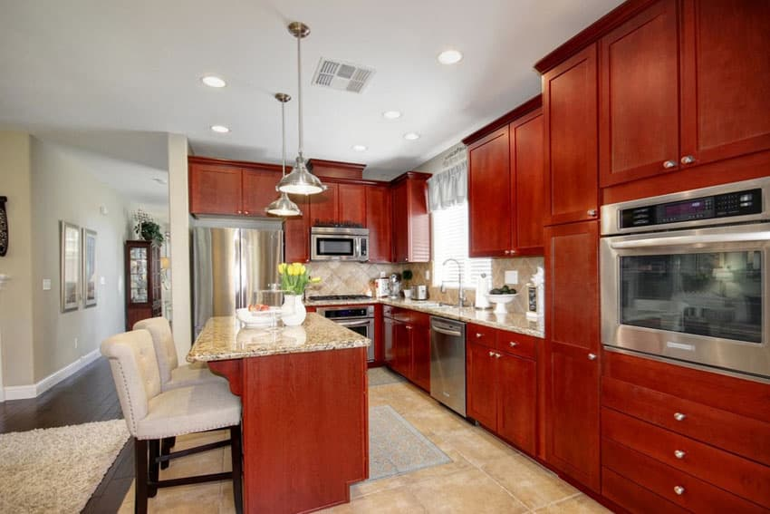 Wood kitchen with eat in island and light color granite counters