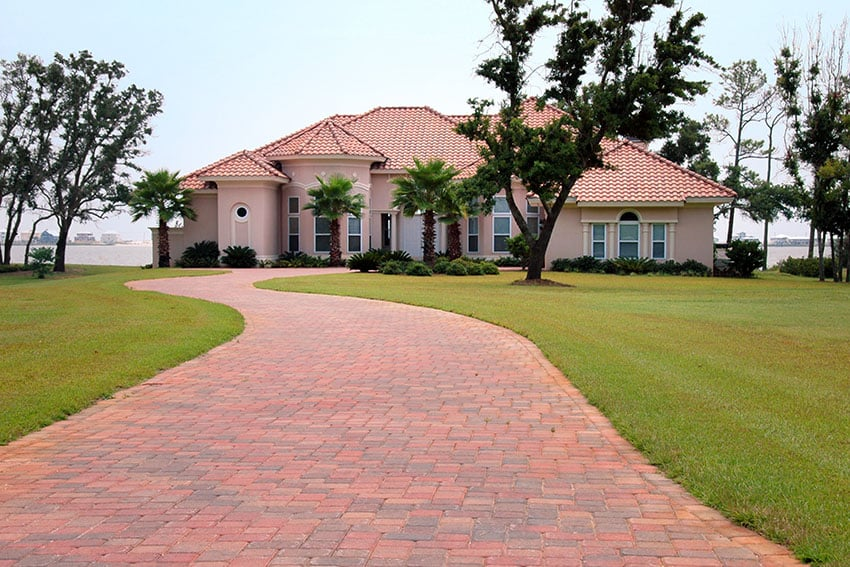 Brick driveway to home with waterfront views