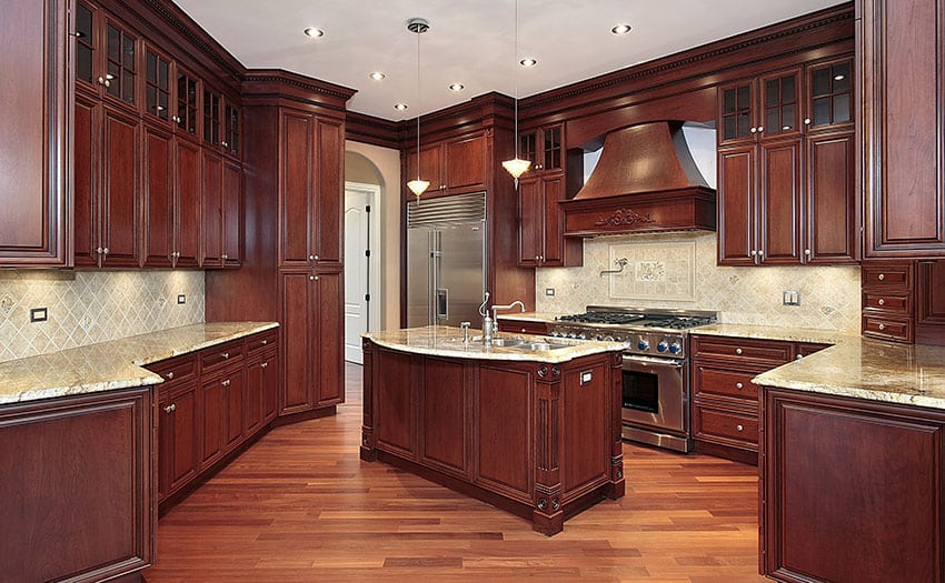 Cherry wood kitchen with light granite counter center island and tile backsplash