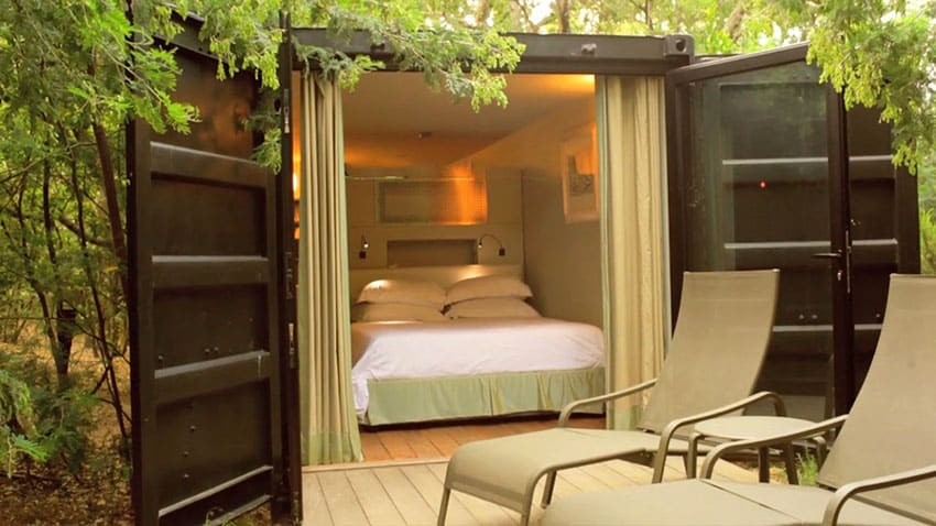 shipping container house bedroom with open doors to outside garden and