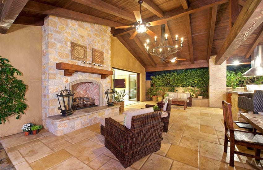 Backyard covered patios - The Large Fireplace Makes A Fun Gathering Place At Night This Space