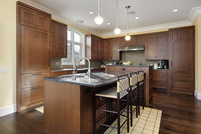 Dark wood cabinet kitchen with black counter dining island