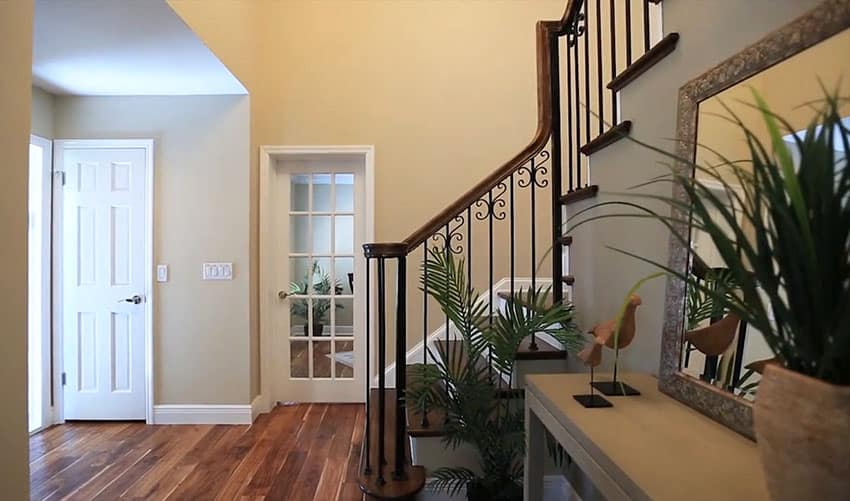 Foyer at Tudor style home with wrought iron staircase