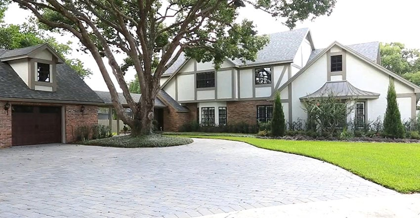 Front of Tudor style home with brick circular driveway
