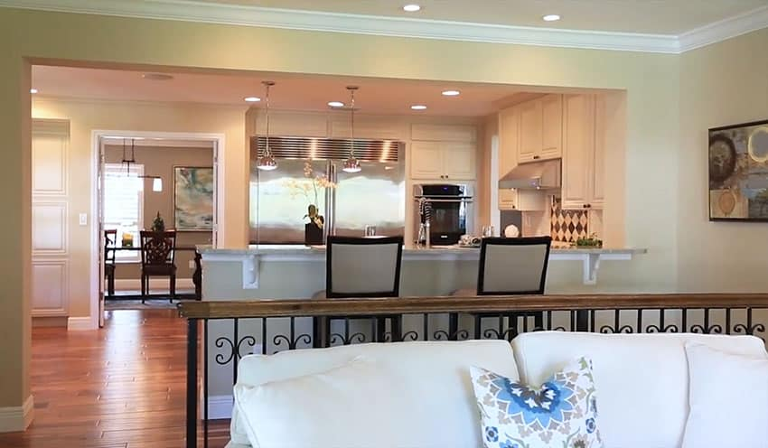 Kitchen with open layout to living room past wrought iron railing