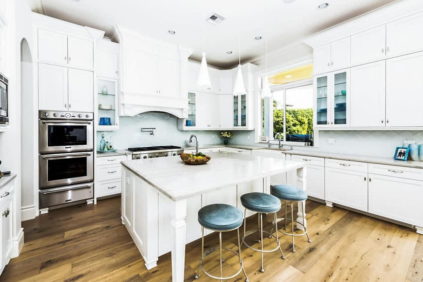 Kitchen with white cabinets carrara marble counter and mini pendant lights