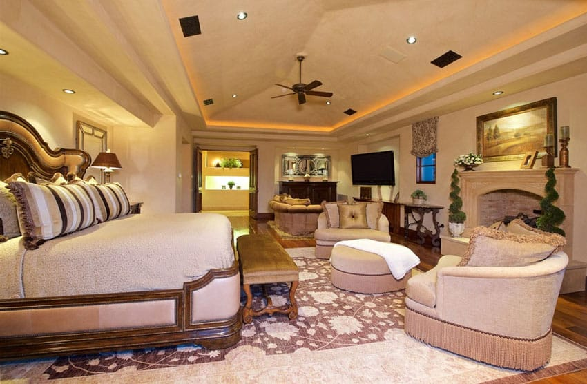 Luxury bedroom with fireplace and raised ceiling with recessed lighting