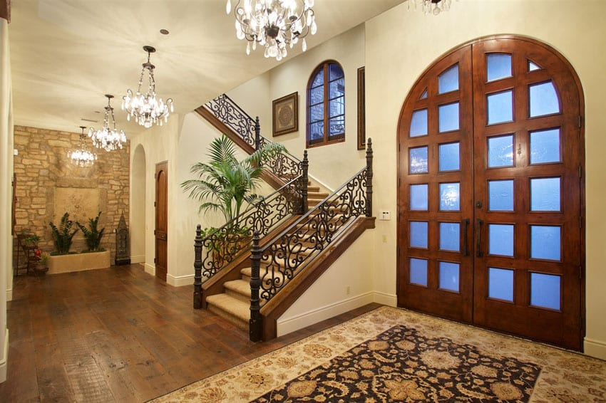 Luxury home foyer with glass chandeliers and large arched doorway