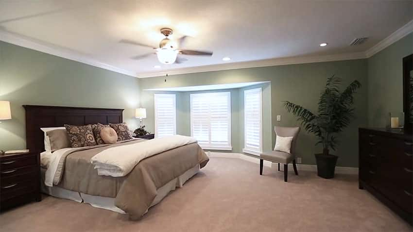 Master bedroom with bay windows, matching furniture and fan