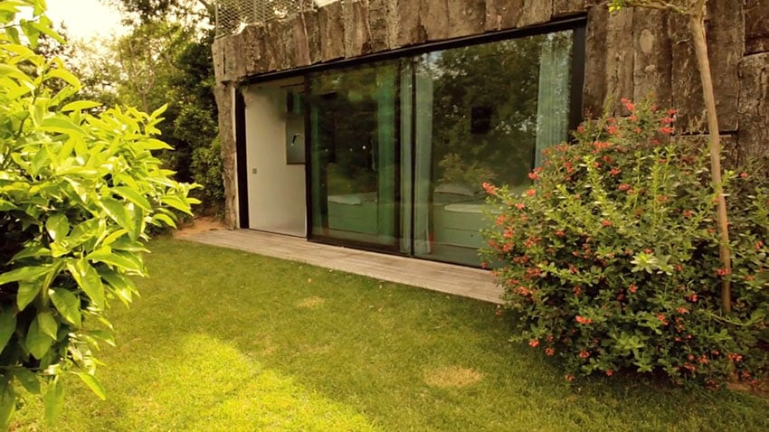 Stone exterior of modern home with sliding door to bedroom