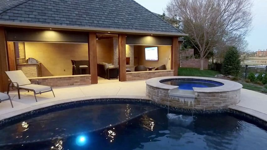 Swimming pool with cabana with motorized shades fireplace