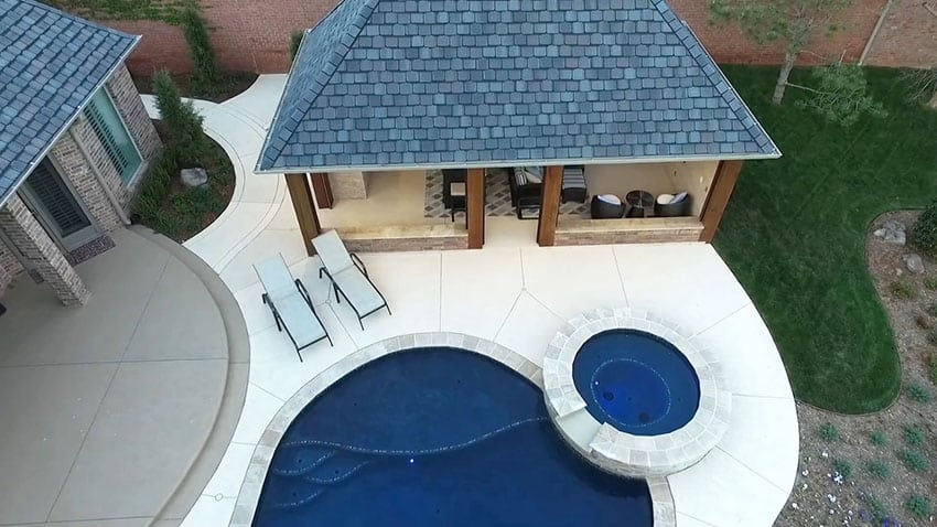 Swimming pool with shingled cabana building with lounge area