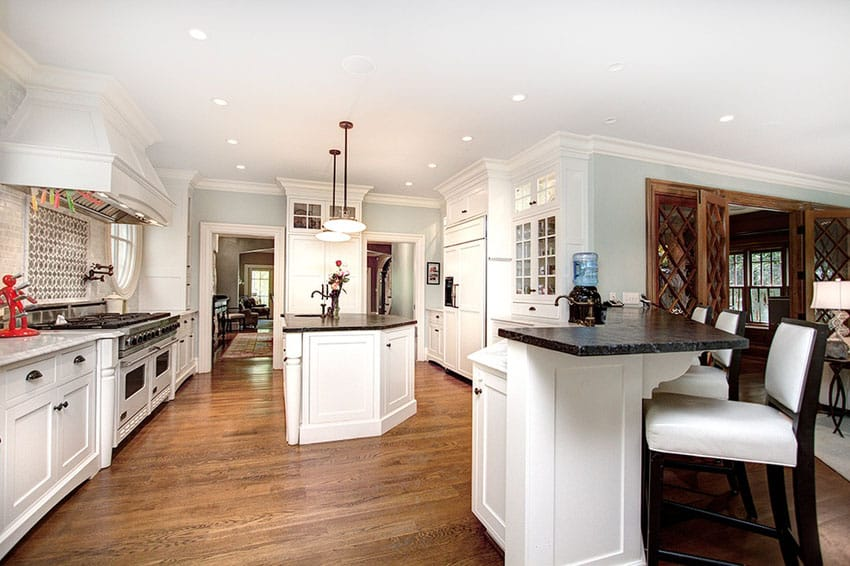 Traditional kitchen with black soapstone counter island, white cabinets and ash hardwood flooring