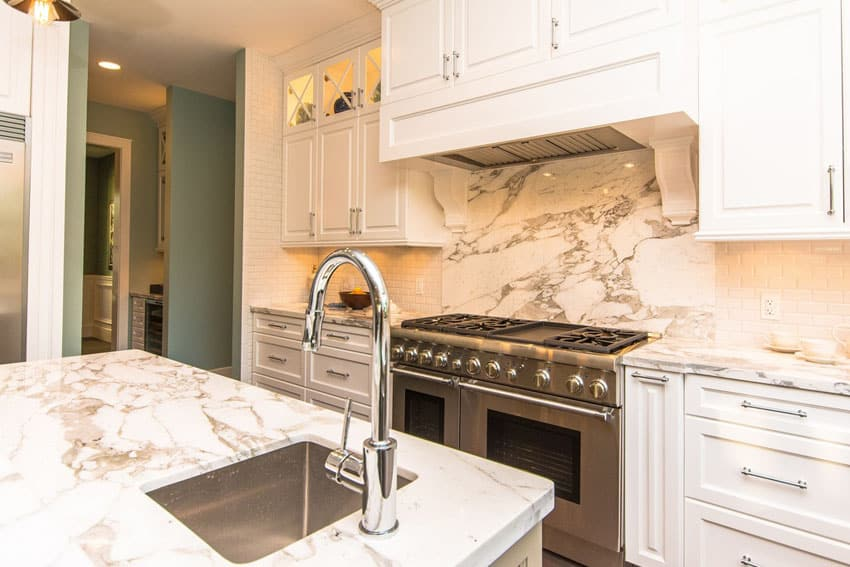 Traditional white cabinet kitchen with marble counters and tile backsplash