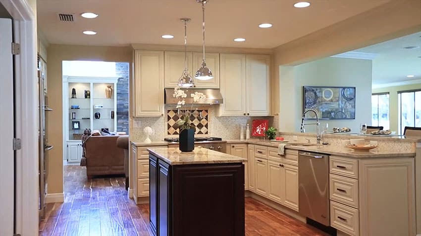 White cabinet kitchen with dark color island and french pendant lights