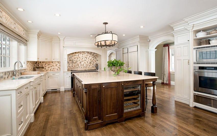 White kitchen with large wood center island and diamond shaped back splash