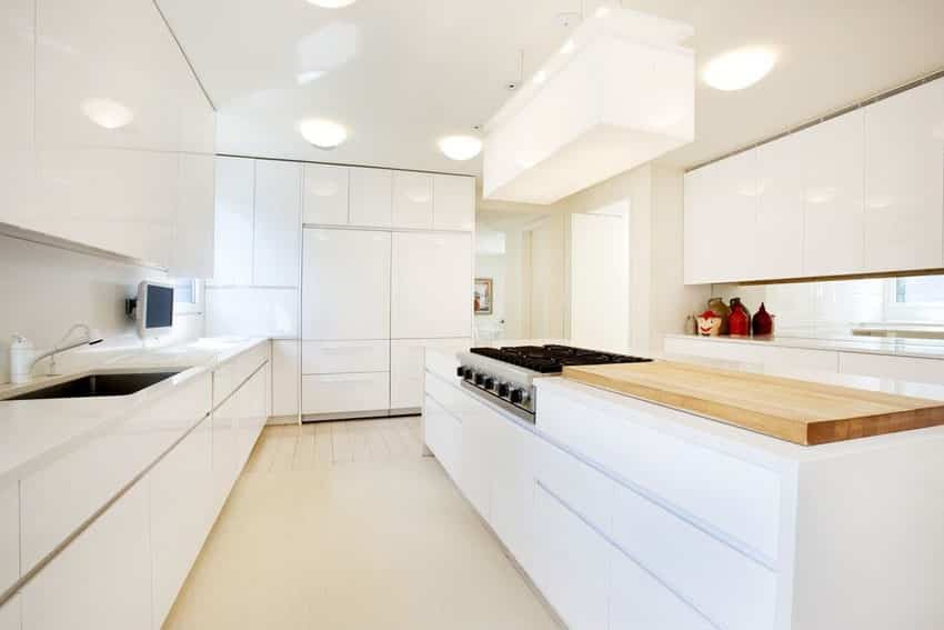 White modern kitchen with hidden fridge and butcher block countertop