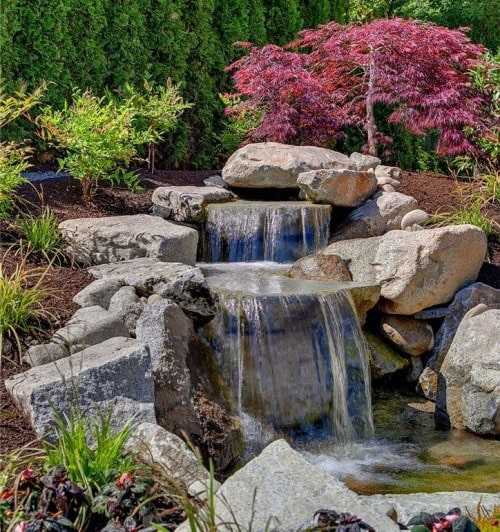 Beautiful rock waterfall with colorful plants in the garden