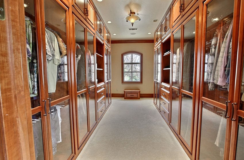 Beautiful wood walk in closet with glass cabinets