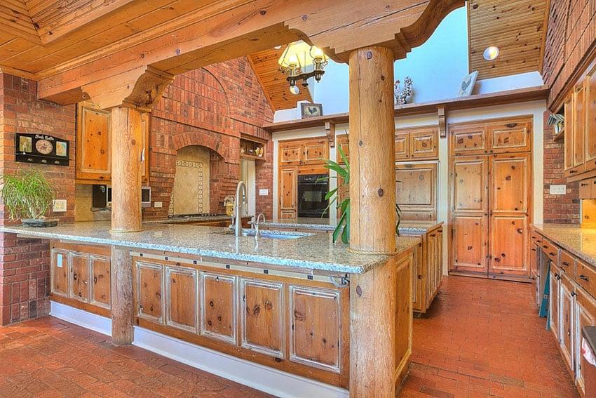 Brick kitchen with wood beams and blanco perla granite counters