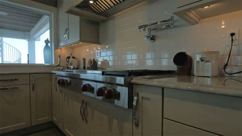 Close up view of stove gourmet kitchen with subway tile