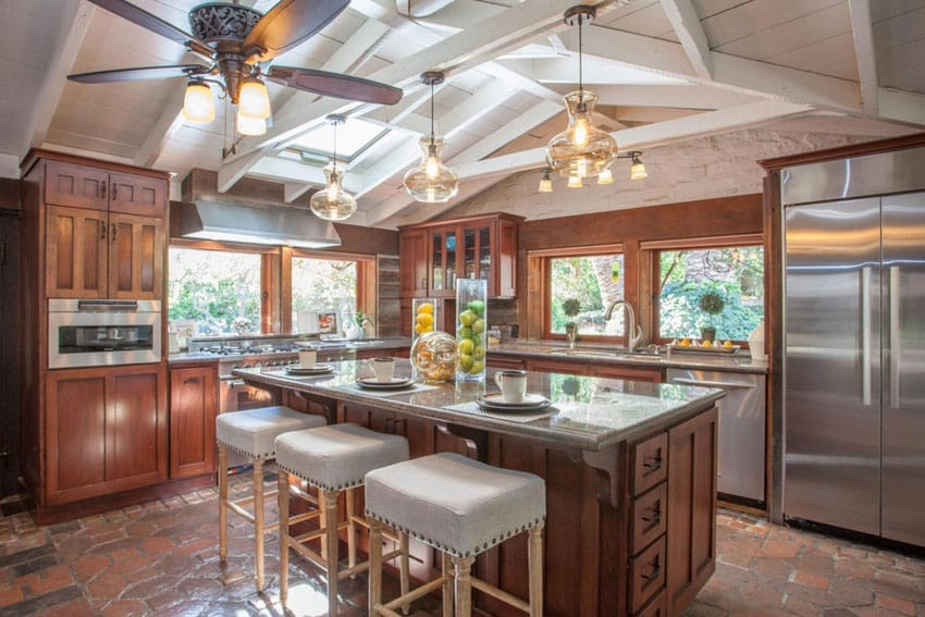 Craftsman kitchen with adobe floor tile and vaulted ceiling