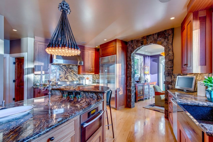 Craftsman kitchen with granite counters, pendant light bundle and hickory floors