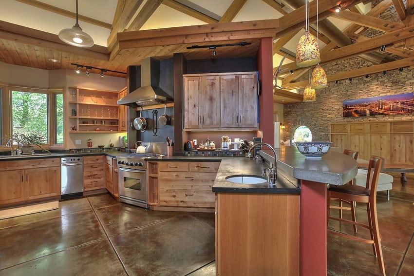 Craftsman kitchen with impala black granite peninsula and concrete floors