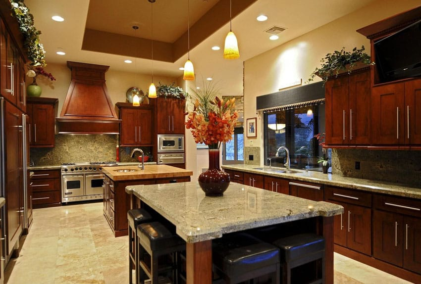 Craftsman kitchen with two islands, marble countertop and tray ceiling