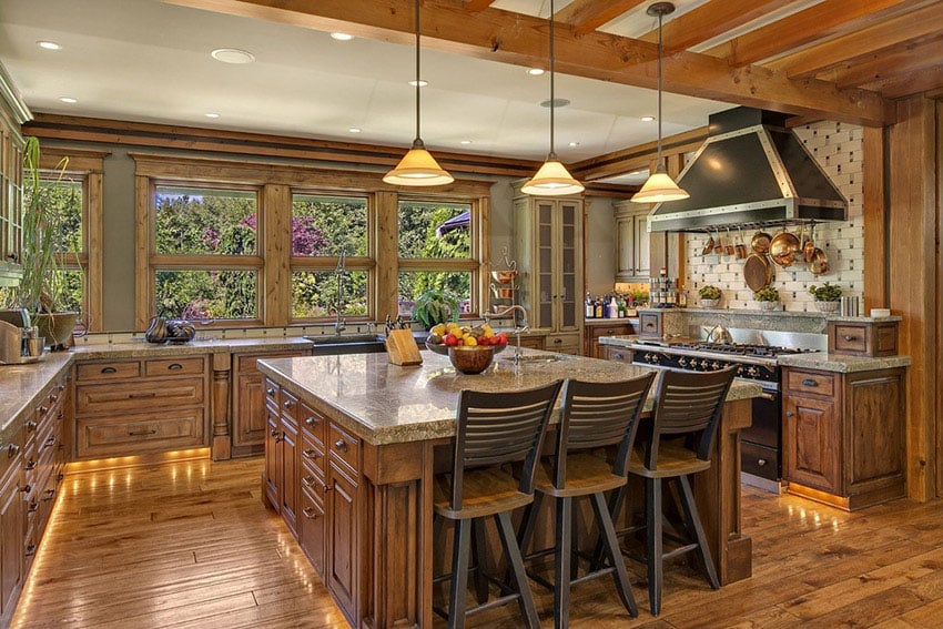 Craftsman kitchen with oversized island, window views and exposed beam ceiling