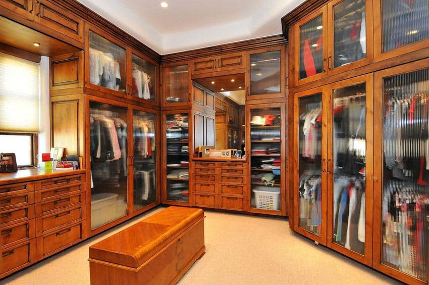 Custom craftsman walk in closet with crown molding frosted glass cabinets