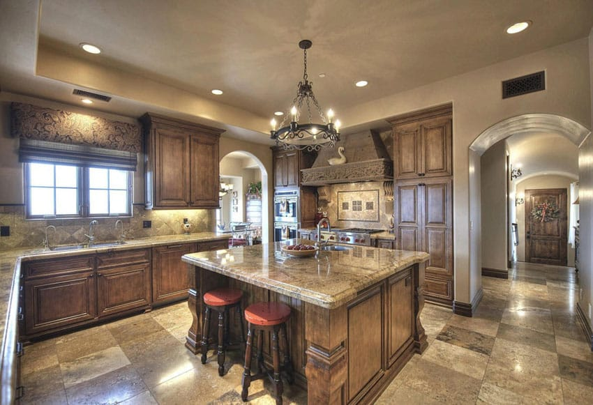 Custom Mediterranean kitchen with rustic iron chandelier large island