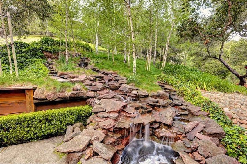 Custom stacked stone stream and waterfall in backyard
