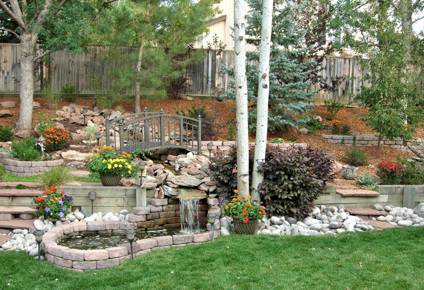 Garden path with waterfall and pond surrounded by brick pavers
