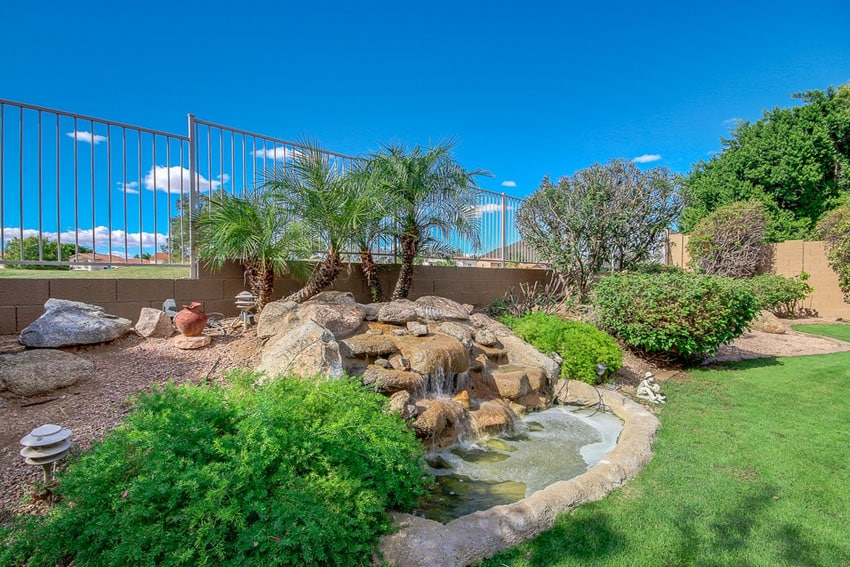 Garden waterfall and small pond in landscaped backyard