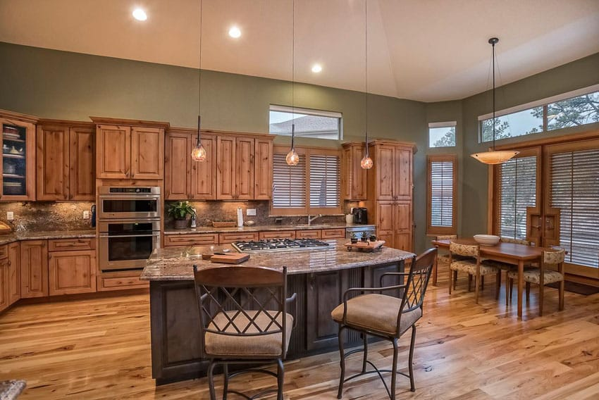 L shaped craftsman kitchen with wood flooring, pendant lights and open to dining table