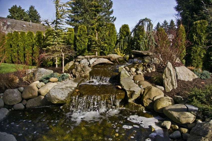 Large natural looking stone waterfall in backyard