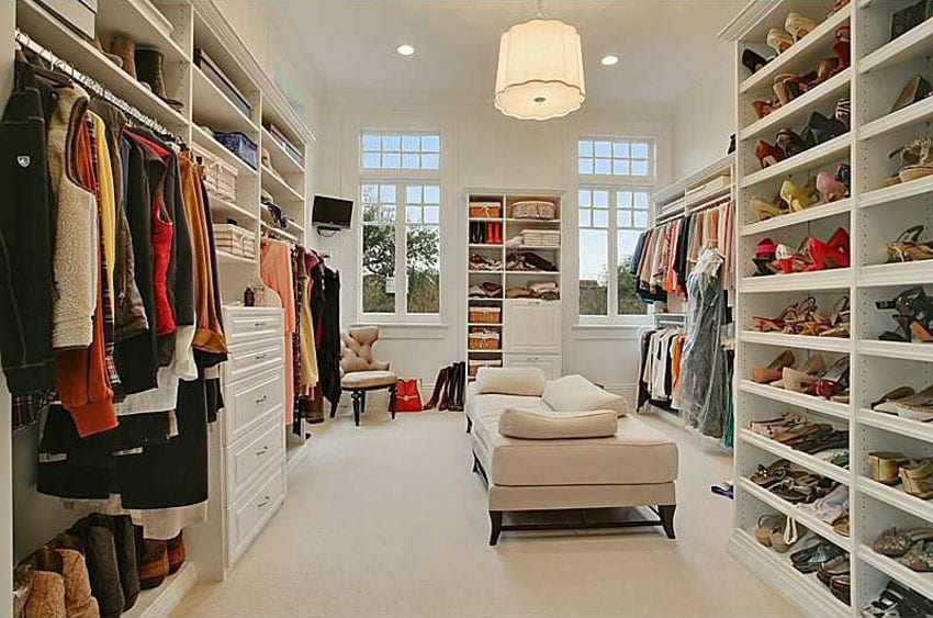 Large walk in closet with white theme and daybed