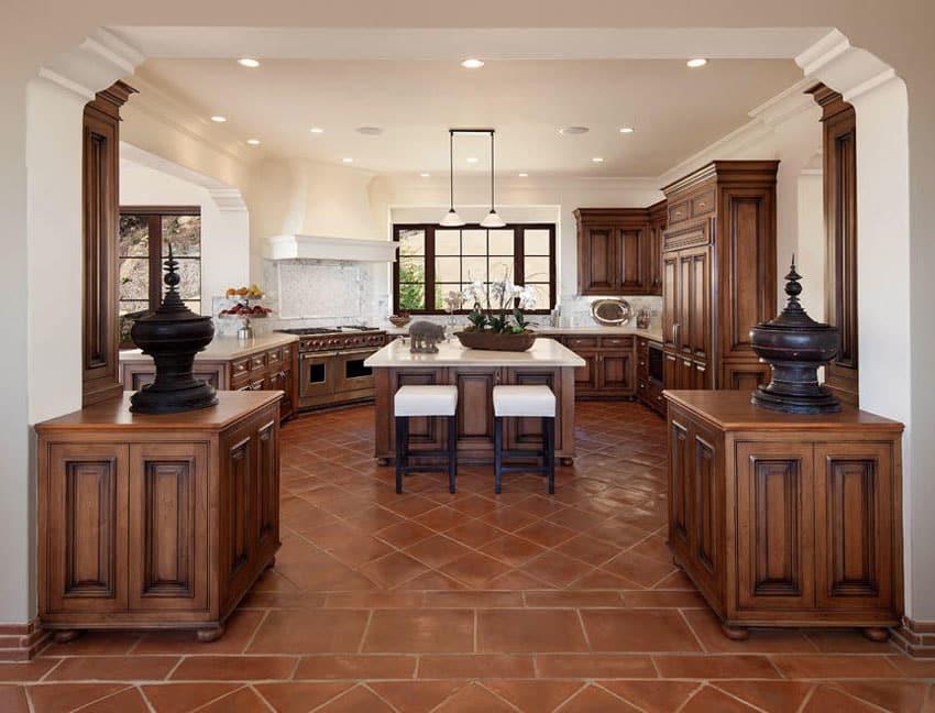 Luxury kitchen with center island molding and terra cotta floors