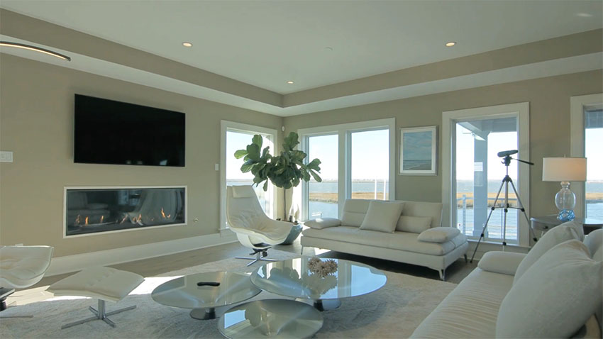 Luxury living room with waterfront views and modern gas fireplace