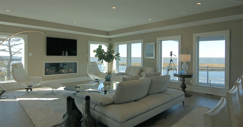 Luxury living room with modern fireplace and wraparound waterfront views