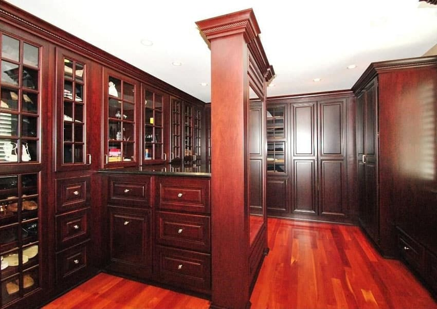 Masculine walk in closet with bright cherry wood floors and raised panel cabinetry